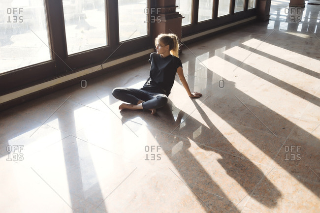 Full length of thoughtful young woman sitting on tiled floor while looking through window