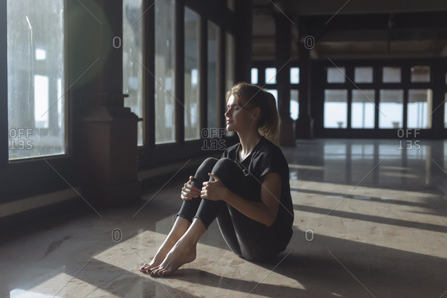 Full length of young woman with eyes closed holding knees while sitting on tiled floor