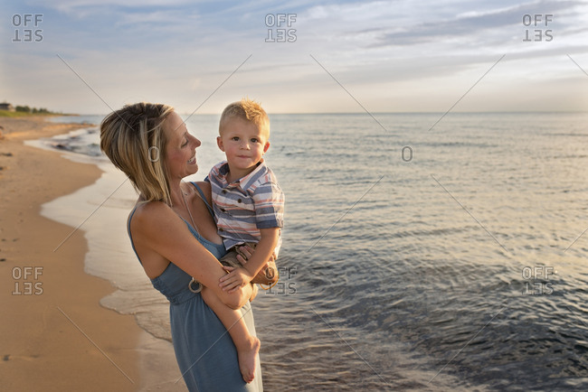 Portrait of cute son carried by mother at beach during sunset