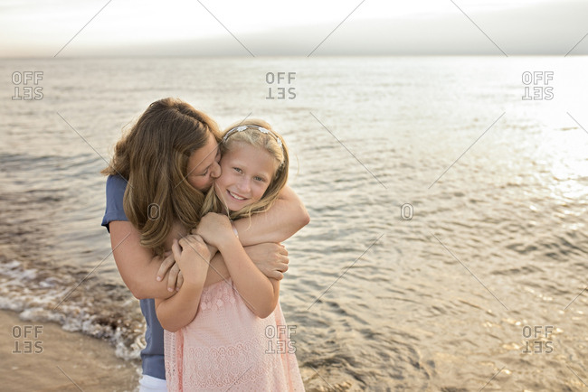 Portrait of cheerful daughter with mother kissing and embracing her at beach during sunset