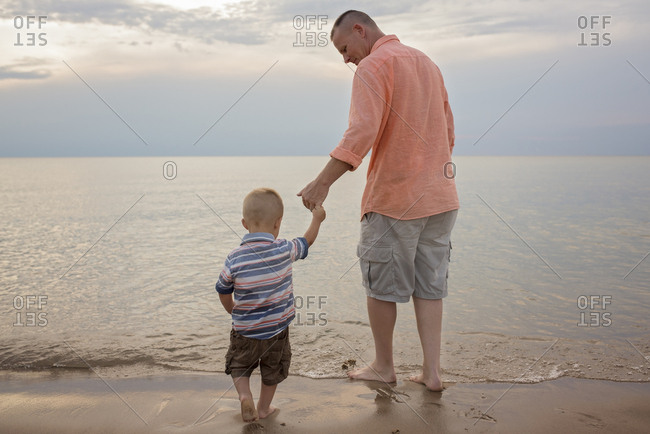 Rear view of father holding son's hand while standing on shore at beach