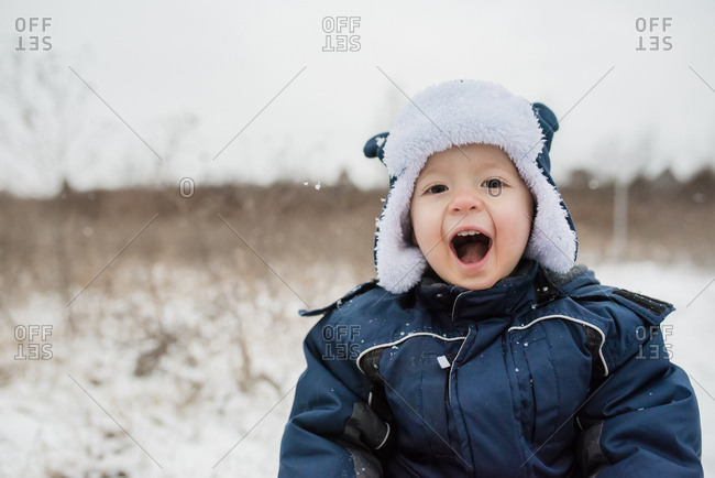 Portrait of cute playful baby boy shouting while wearing warm clothing during winter