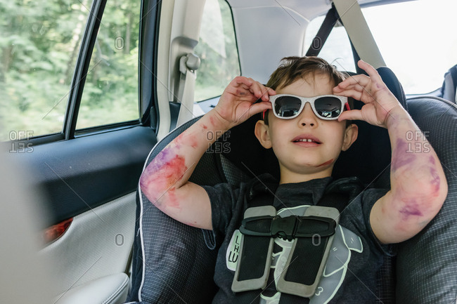 Young boy with marker on arms tries on baby sister's sunglasses in back seat of car