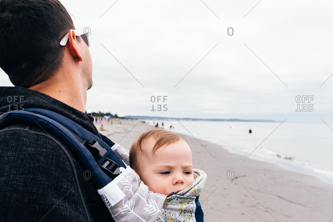 Sleepy baby looking suspiciously out of baby carrier on dad's chest