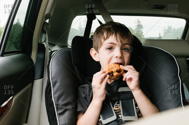 Young boy eating a pain au chocolat in the back seat of car