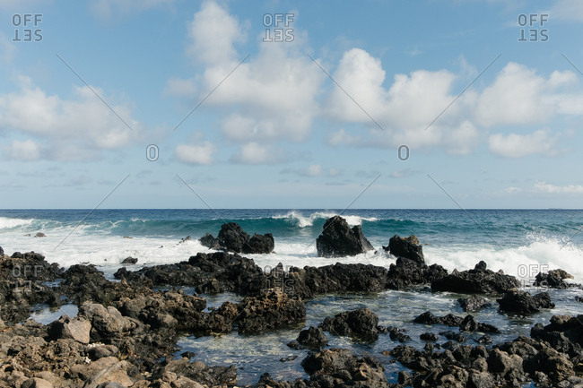Waves breaking against rocks on rocky shoreline in Hawaii