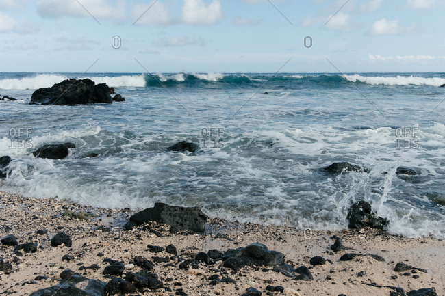 Waves breaking along rocky beach in Hawaii