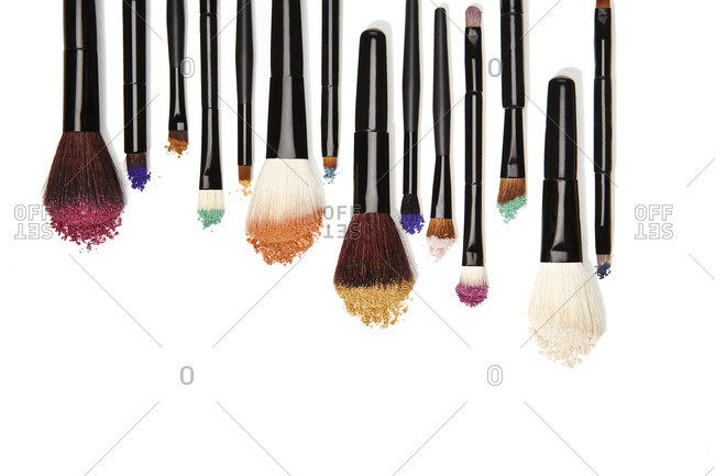 Top down studio shot of variety of make up brushes with powdered ends
