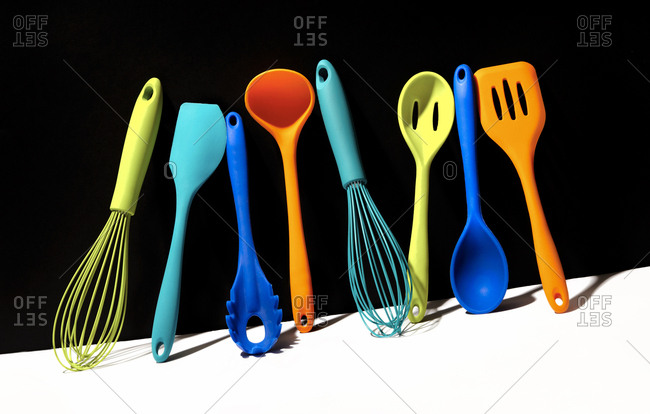 Studio shot of multi-colored kitchen utensils standing up ...
