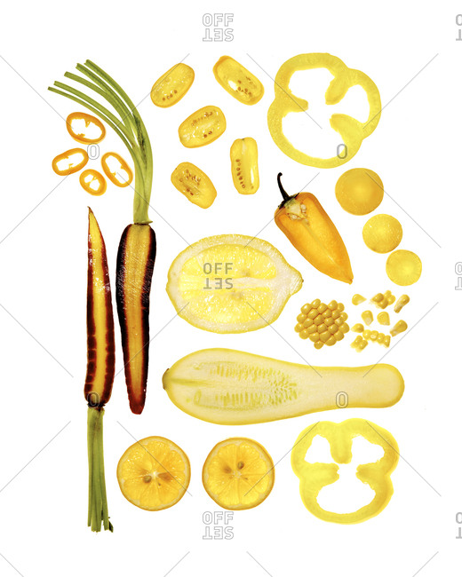 Top down view of artfully arranged sliced yellow and orange fruits and vegetables