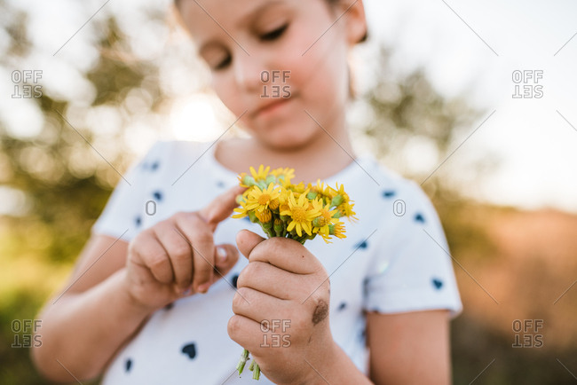 Looking up at little girl counting petals on flowers