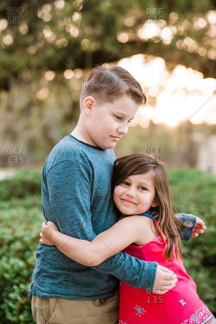 Young girl grabs older brother for spontaneous hug