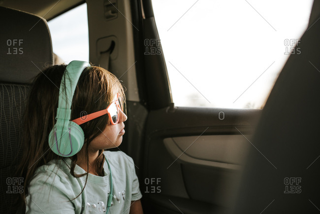 Young girl wearing sunglasses and headphones sitting in back seat of car looking out of the window
