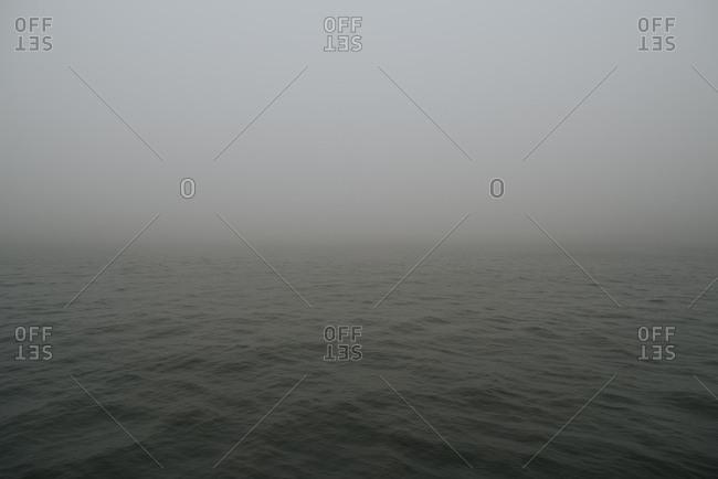 Fog settling over empty dark grey ocean
