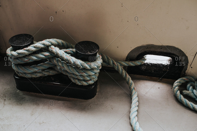 Mooring line wrapped around bitts on deck of ship