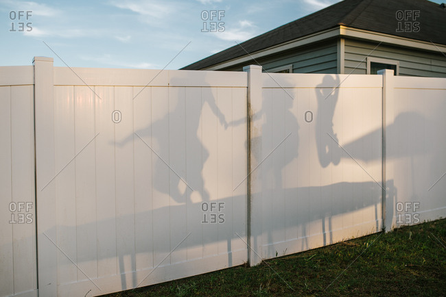 Kids jumping on trampoline casting shadow on backyard fence