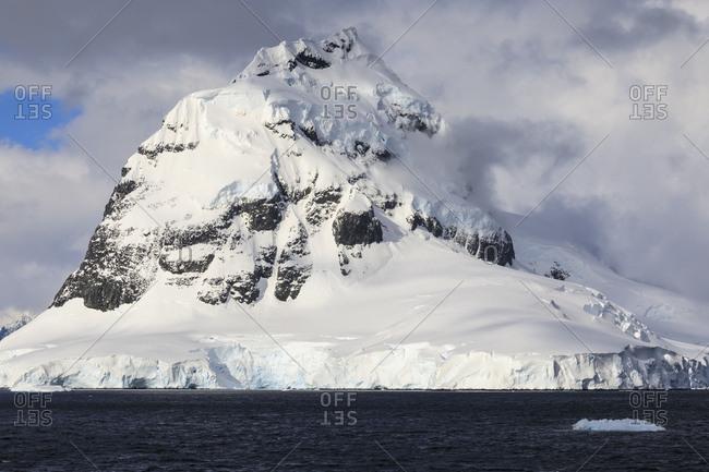 Glaciers, pyramidal mountain peak and dramatic clouds and sky, Cape Errera, Wiencke Island, Antarctic Peninsula, Antarctica, Polar Regions