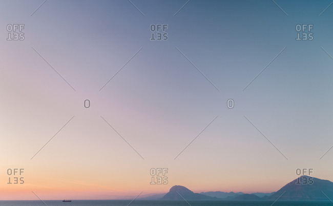 Aerial view of fishing boat on horizon at sunset in Patras, Greece