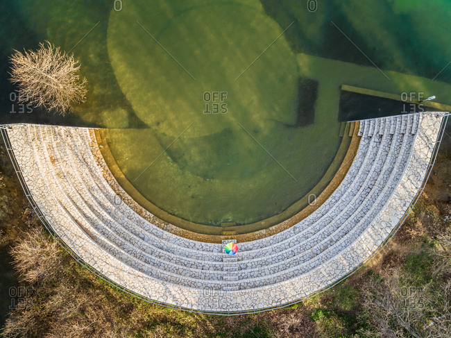 Aerial view of rainbow umbrella at old amphitheater at lake Plastira in Greece