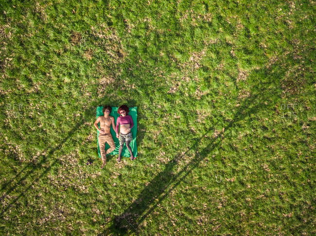 Aerial view of happy young man and pregnant woman holding hands while lying in grass at park