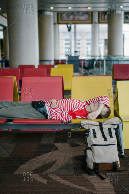 Tired woman sleeping on airport seats