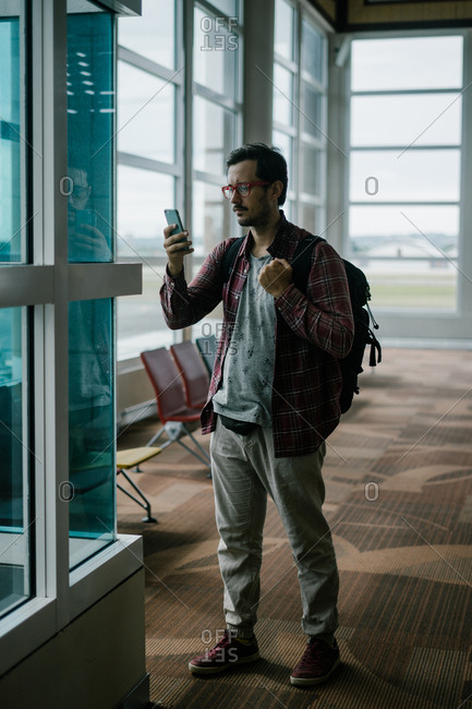Man using cell phone while waiting in an airport terminal