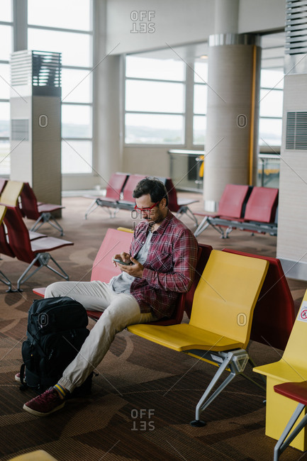 Man using cell phone while sitting in an airport terminal