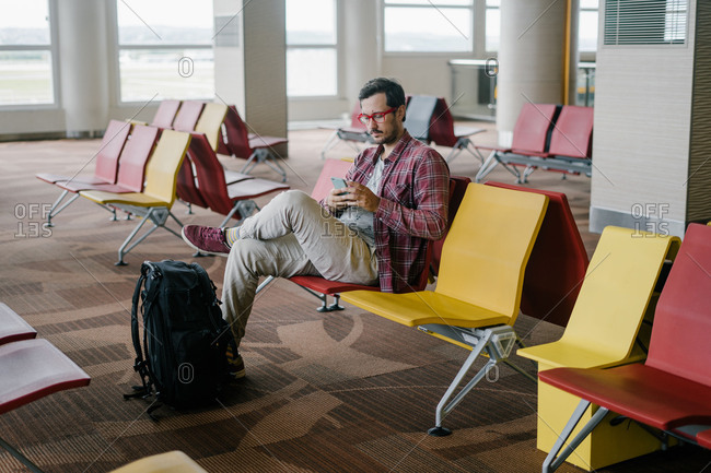 Man sitting in an airport terminal using cell phone
