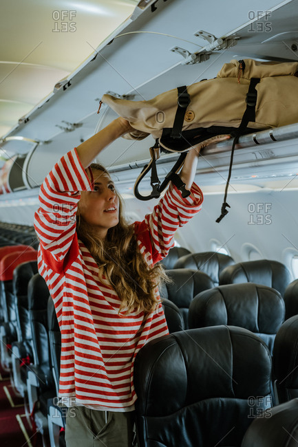Woman putting bag into overhead compartment on an airplane