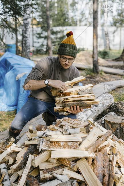 Man gathering chopped firewood