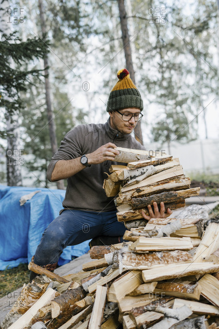 Man collecting chopped firewood