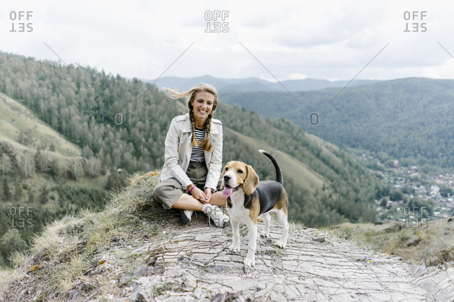 Young woman sitting on a hill with a dog in Krasnoyarsk, Russia