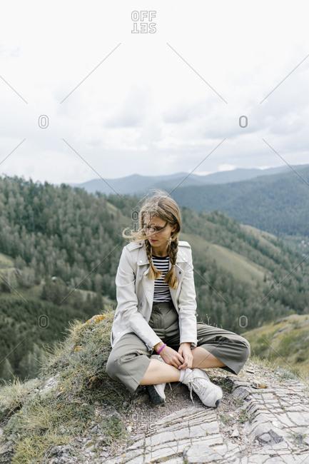 Young woman sitting on a hill in Krasnoyarsk, Russia