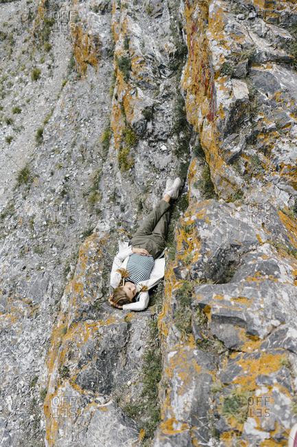 Overhead view of woman lying on a rocky mountain in Krasnoyarsk, Russia