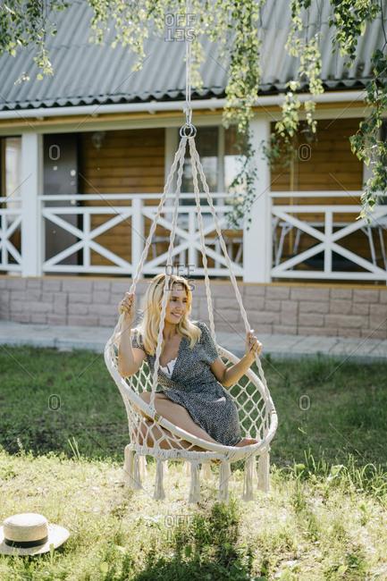 Woman sitting in a macrame swing