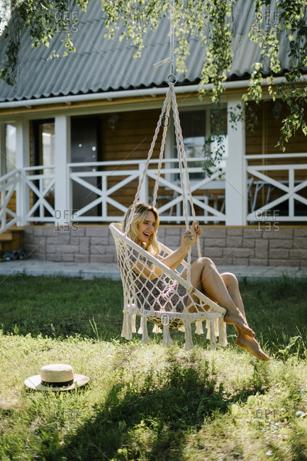 Smiling woman sitting in a macrame swing