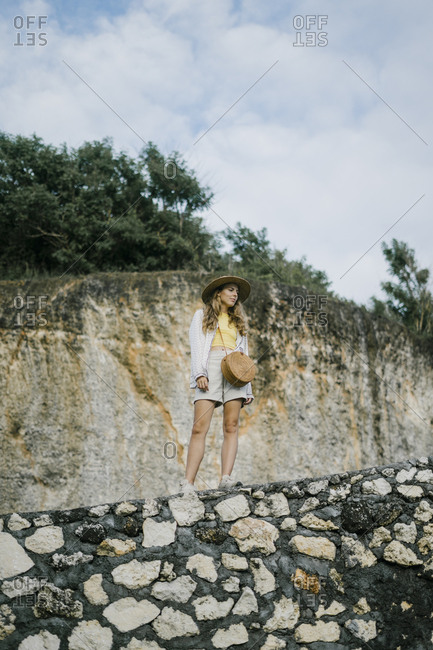 Young woman standing on rocky mountainside in Bali