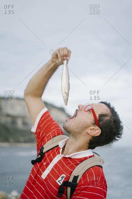 Man pretending to eat raw fish