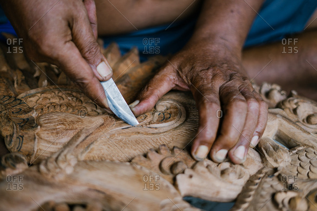Man hand-crafting wood relief carvings