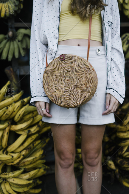 Bali visitor standing in front of bananas with wicker purse