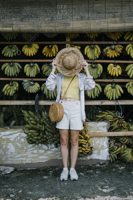 Female tourist playfully covering face with straw hat at fruit stand