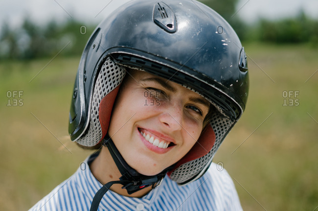 Woman driver with helmet smiling in the bright sun