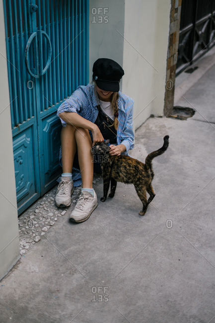 Blonde woman petting cat outside Vietnamese building