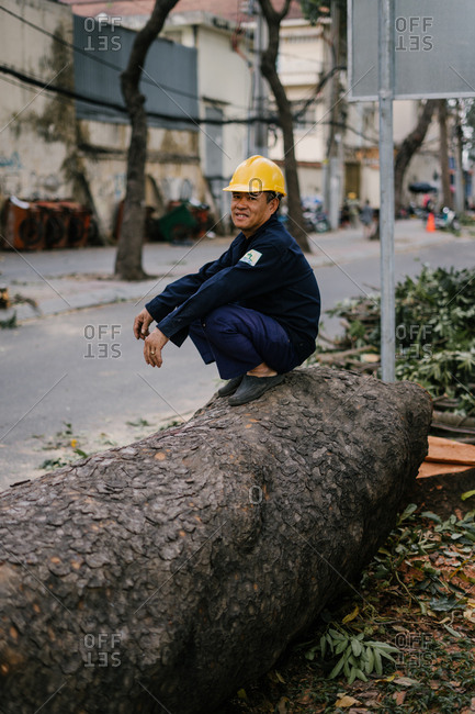 Ho Chi Minh City, Vietnam - January 8, 2018: Male construction worker taking break on large tree log in the city