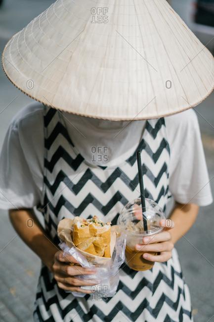 Female pedestrian eating to-go lunch in Vietnamese street