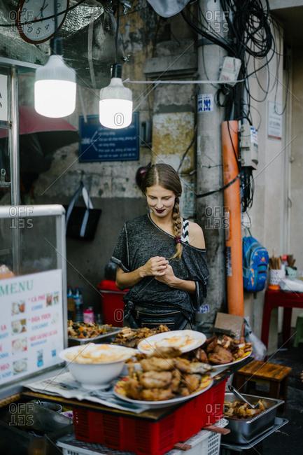 Tourist ordering dinner from Vietnamese food vendor