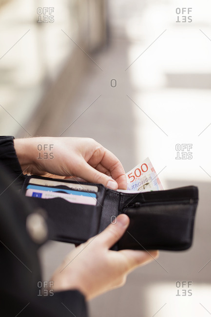 Hands holding a wallet with Swedish currency