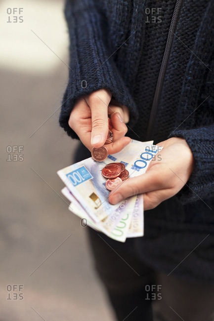 Hands holding Swedish currency