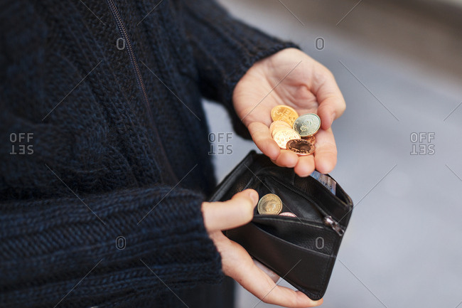 Person placing coins in wallet