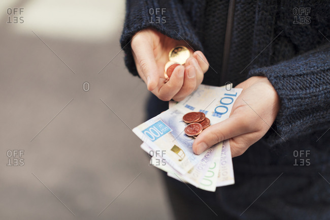 Hands holding coins and currency